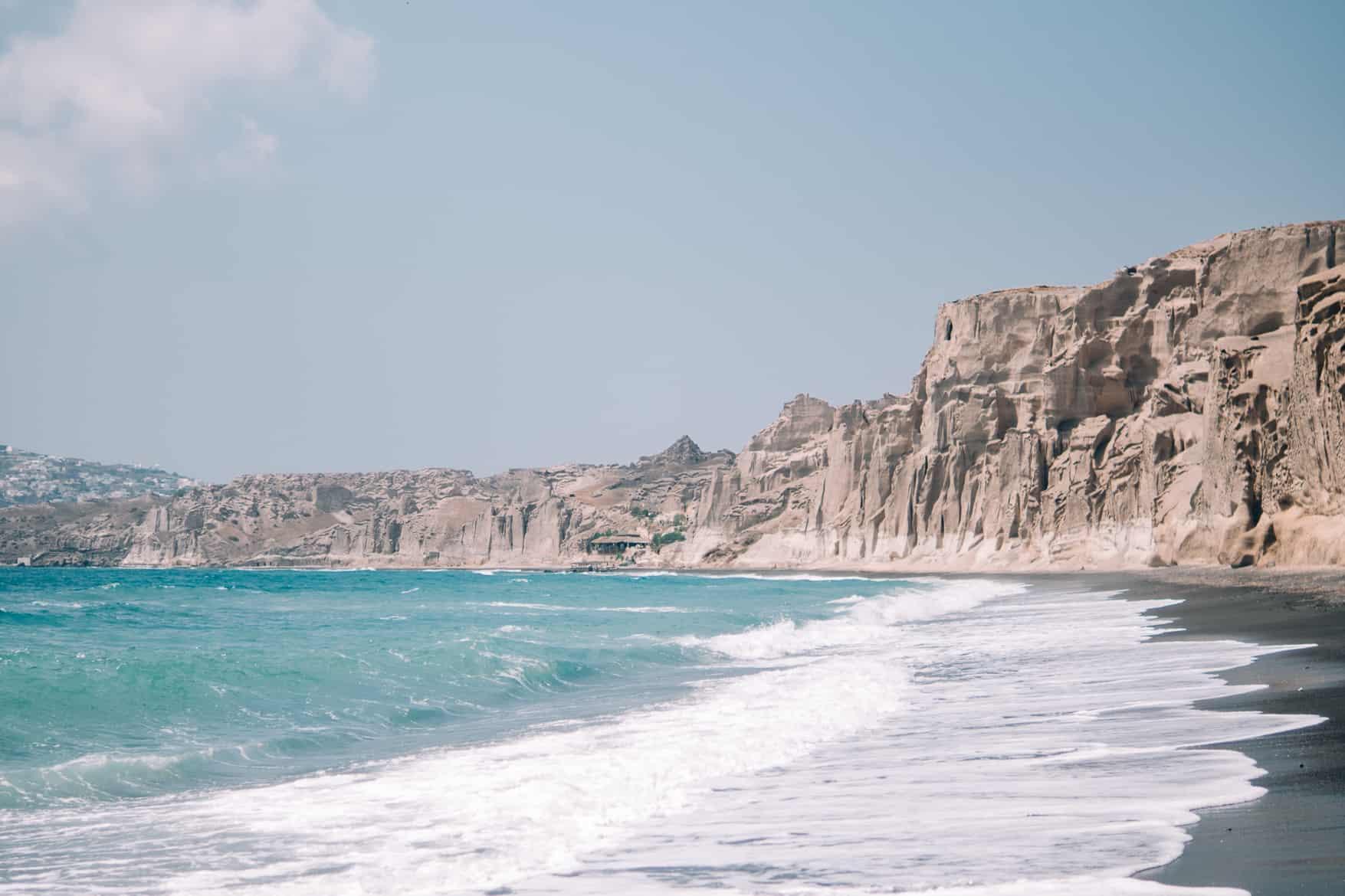 Santorini Travel Guide: Klares Wasser vor schroffen Felsen am Vlychada Beach